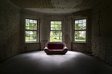a red sofa in a dark room in an abandoned hospital in Germany - ARC101291