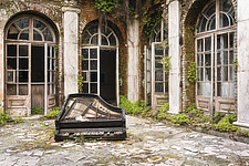 a piano on the floor in a room in an abandoned palace in Poland - ARC101294