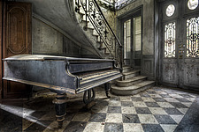 a piano standing in the hallway with a staircase in an abandoned villa in France - ARC101317