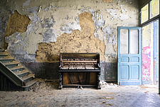Abandoned piano against the wall at a factory in Belgium - ARC102840