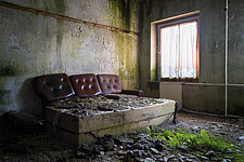 Furniture in the rooms in an abandoned hotel in Germany, with plants or moss on the floor - ARC102845