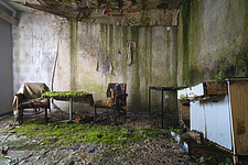 Furniture in the rooms in an abandoned hotel in Germany, with plants or moss on the floor - ARC102846