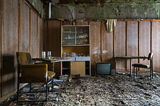 Furniture in the rooms in an abandoned hotel in Germany, with plants or moss on the floor - ARC102848