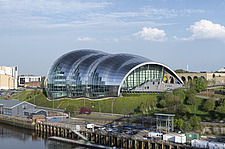 A sunny day shot from the High Level bridge, River Tyne in foreground, Sage full facade above on the Gateshead side, on landscaped bank - ARC104130