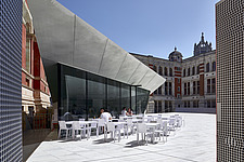 Visitors sit at the cafe enjoying the sun in the new Sackler Courtyard at the V&A, London, UK, completed in 2017 - ARC104227