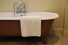 Bath towel draped over the edge of a freestanding bath - ARC104358
