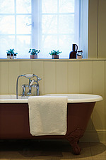 Bath towel draped over the edge of a freestanding bath - ARC104359