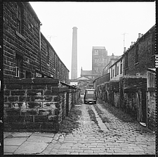 Car parked in the cobbled ginnel (alley) running between Milton Street and Tentre Street viewed from Richard Street with Pentridge Mill and mill chimn... - ARC104719