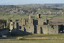 Middleham Castle from the South, with the village of Middleham in the distance, Wensleydale, North Yorkshire, England, UK - ARC104726