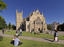 General view of Exeter cathedral from the north-west, with people relaxing on the lawns in the foreground, Devon, England, UK - ARC104730