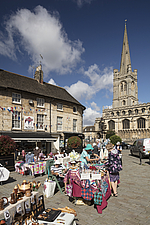 Street market on Red Lion Square, with All Saints church in the background, Stamford, Lincolnshire, England, UK - ARC104743