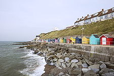 Painted beach huts on the East Promenade in Sheringham, Norfolk, England, UK seen from the West - ARC104766