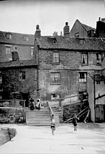 A view along Tate Hill Pier towards houses on Tate Hill in Whitby, with two children in the foreground, North Yorkshire, UK - ARC105381
