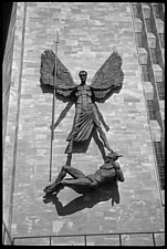 Jacob Epstein sculpture of St Michael over Lucifer holding a long spear, arms and wings outstretched, with Lucifer's feet and arms bound, on the exter... - ARC105387