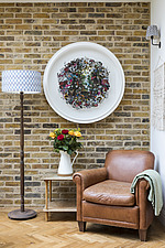 Armchair and standard lamp in the corner of the kitchen in a redesigned and remodelled family home in West London, UK - ARC105822