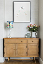 A sideboard in the corner of the living room in a redesigned and remodelled family home in West London, UK - ARC105827