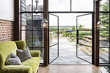 Sofa next to open doors leading out to the garden of a converted barn/mill in Essex, UK, featuring beautful steel windows - ARC105870
