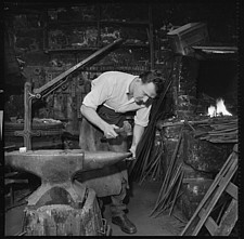Blacksmith working in smithy, using hammer and anvil - ARC107496
